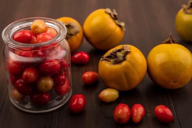 Vista superior de cerejas vermelhas da cornalina em uma jarra de vidro com frutos de caqui isolados em uma superfície de madeira