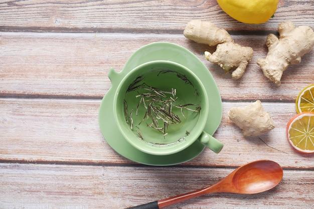 Vista superior de chá verde e folhas de ervas em uma pequena tigela de vidro na mesa