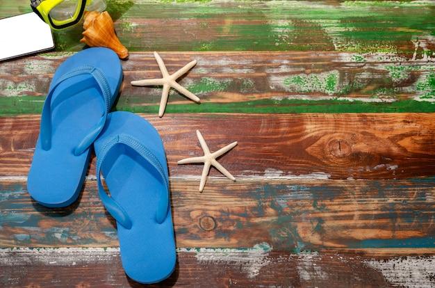 Vista superior de chinelos, smartphone, snorkel, conchas e estrelas do mar na mesa de madeira