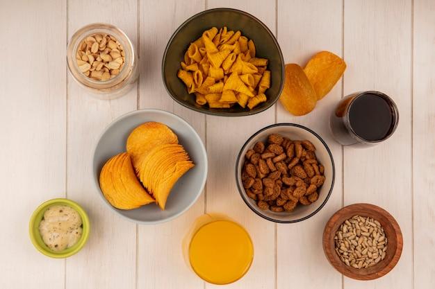 Vista superior de chips crocantes em uma tigela com pinhões em uma jarra de vidro com molho em uma tigela verde com pequenas bolachas de centeio em uma tigela com um copo de coca-cola e suco de laranja em uma mesa de madeira bege