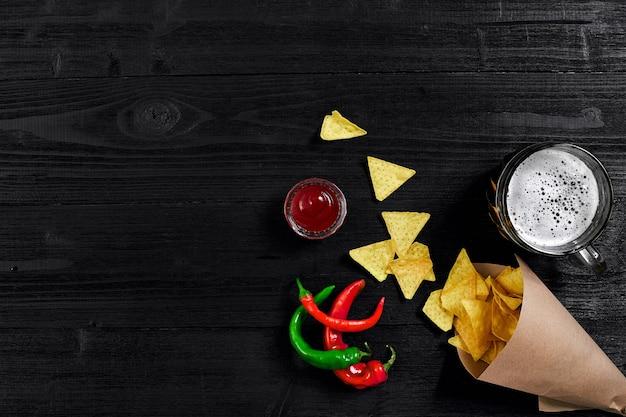 Vista superior de chips de tortilha com copo de molho de cerveja e pimenta vermelha em fundo preto de madeira