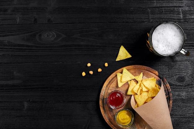 Vista superior de chips de tortilha com copo de molho de cerveja no fundo preto de madeira