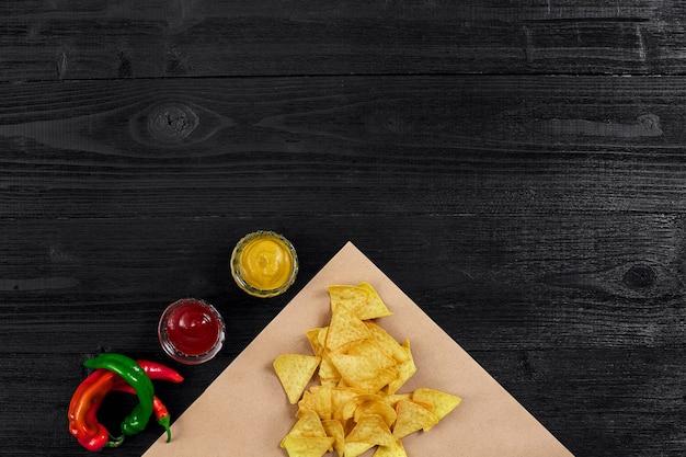 Vista superior de chips de tortilha com molho e pimenta malagueta vermelha em fundo preto de madeira