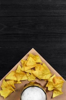 Vista superior de chips de tortilha e copo de cerveja em fundo preto de madeira