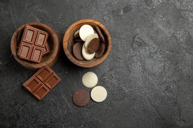 Vista superior de chocolate com chocolate em tigelas de madeira sobre a mesa