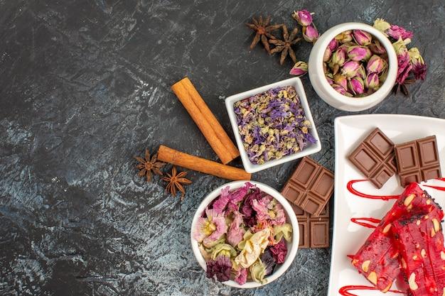 Vista superior de chocolates em prato branco com tigelas de flores secas e canela em fundo cinza