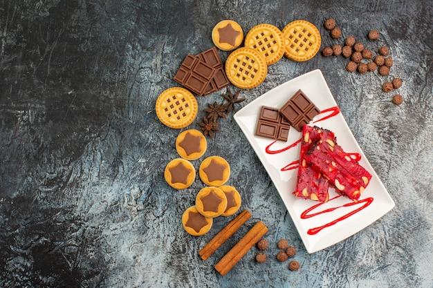 Vista superior de chocolates em um prato branco com muitos doces deliciosos em um fundo cinza