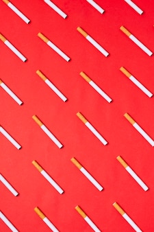 Vista superior de cigarros em fundo vermelho