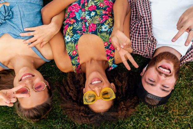 Vista superior de cima em colorida elegante feliz jovem companhia de amigos deitados na grama no parque, homens e mulheres se divertindo juntos