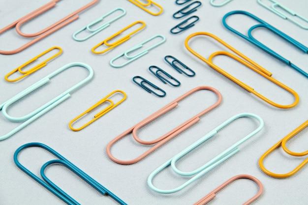 Vista superior de clipes de papel coloridos sobre o fundo pastel