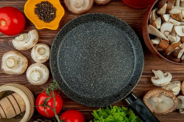 Vista superior de cogumelos brancos frescos com tomate pilão de madeira com ervas secas pimenta preta, dispostas em torno de uma frigideira na mesa de madeira rústica