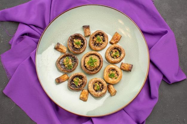 Vista superior de cogumelos cozidos dentro do prato em um prato de tecido roxo, cozinhando o jantar de cogumelos