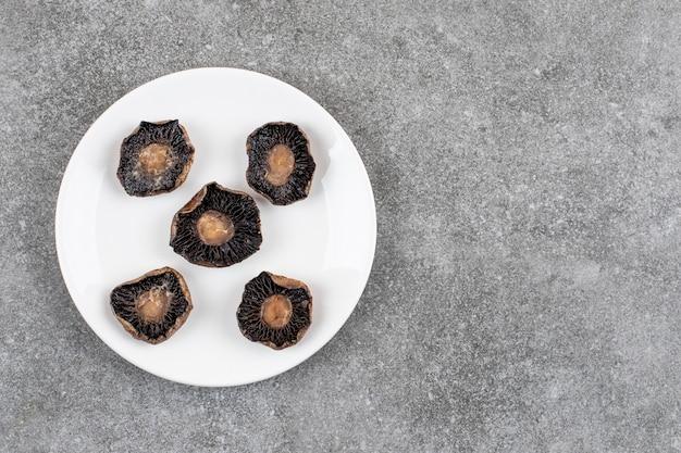 Vista superior de cogumelos cozidos em um prato branco sobre uma superfície cinza