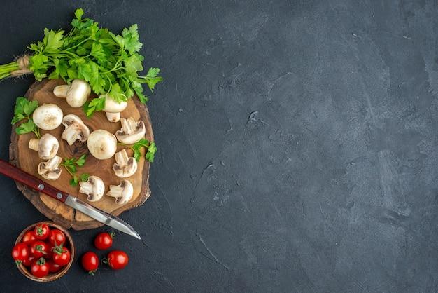 Vista superior de cogumelos crus e faca de verduras na placa de madeira, toalha branca e tomates frescos em uma tigela com fundo preto com espaço livre