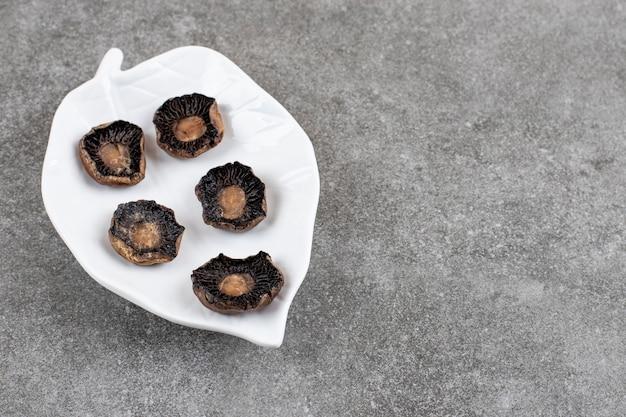 Vista superior de cogumelos frescos cozidos em prato branco