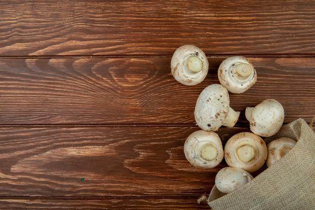 Vista superior de cogumelos frescos espalhados de um saco na superfície de madeira rústica, com espaço de cópia