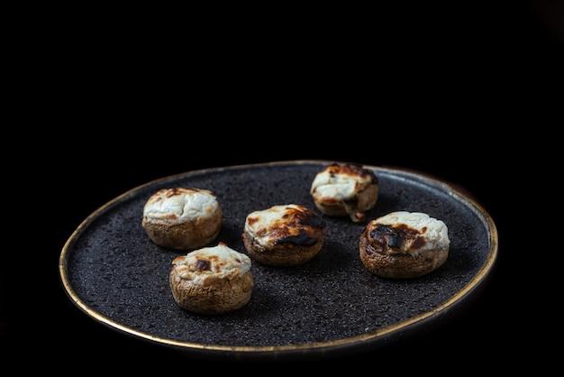 Vista superior de cogumelos recheados em um prato com textura preta e bordas douradas