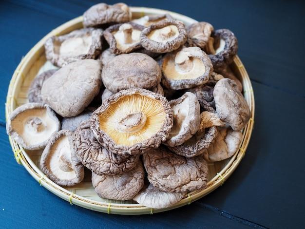 Vista superior de cogumelos shiitake secos na bandeja de tecer bambu na mesa de madeira preta.