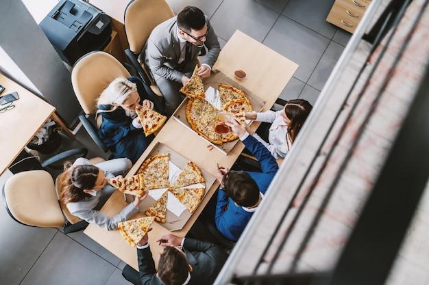 Vista superior de colegas famintos, sentados à mesa e comendo pizza no almoço. interior da empresa corporativa.