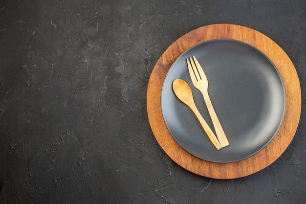 Vista superior de colher de pau e garfo em preto em placas marrons na superfície de cor escura