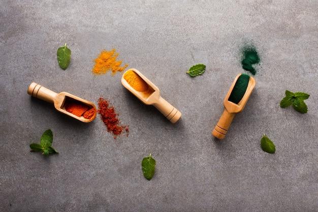 Vista superior de colheres de pau com especiarias aromáticas