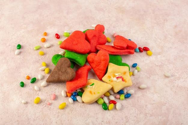 Vista superior de coloridos deliciosos biscoitos diferentes formados com doces na superfície rosa