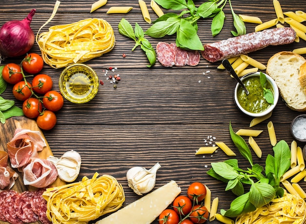 Vista superior de comida tradicional italiana, aperitivos e lanches como salame, presunto, queijo, pesto, ciabatta, azeite de oliva, macarrão em fundo de madeira rústico