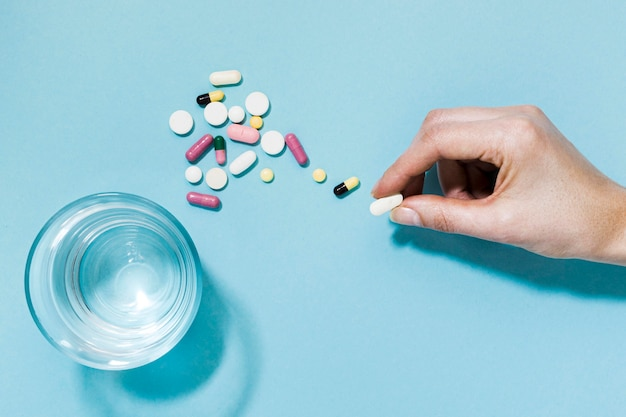 Vista superior de comprimidos com copo de água e mão