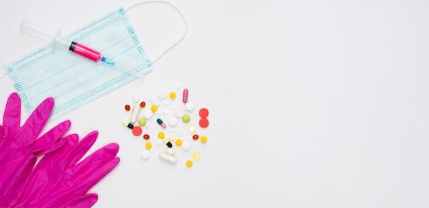 Vista superior de comprimidos com luvas cirúrgicas e máscara médica