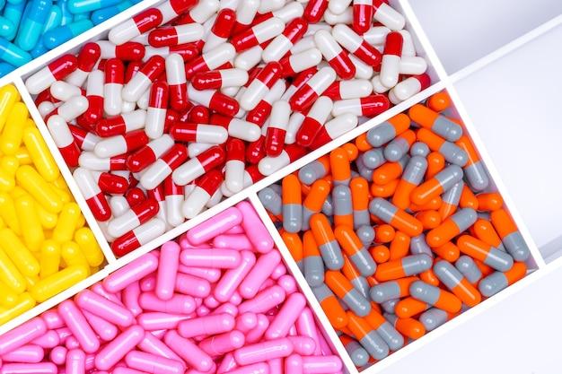 Vista superior de comprimidos de cápsulas de antibióticos em uma bandeja de plástico para medicamentos