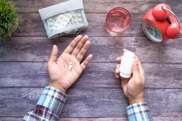 Vista superior de comprimidos médicos na palma da mão na mesa