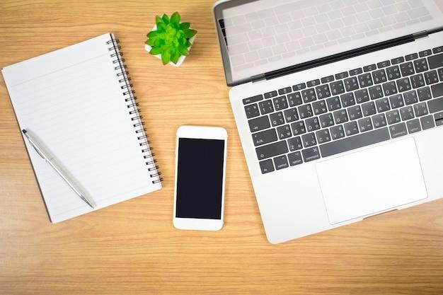 Vista superior de computadores, laptops e dispositivos em uma mesa de madeira de estilo moderno.