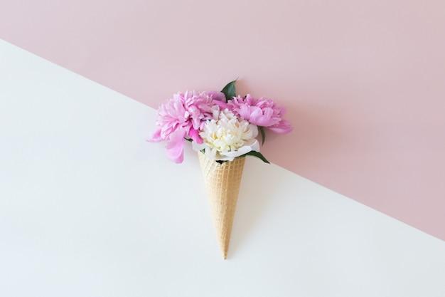 Vista superior de cones de waffle com flores de peônia em rosa pastel