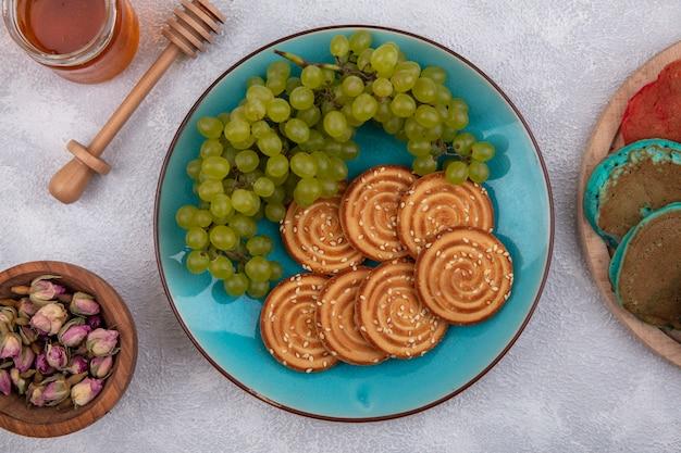 Vista superior de cookies com uvas verdes em um prato azul com mel e botões secos em um fundo branco