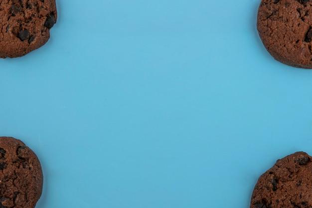 Vista superior de cookies de brownie de farinha de amendoim sem farinha nos lados sobre fundo azul, com espaço de cópia