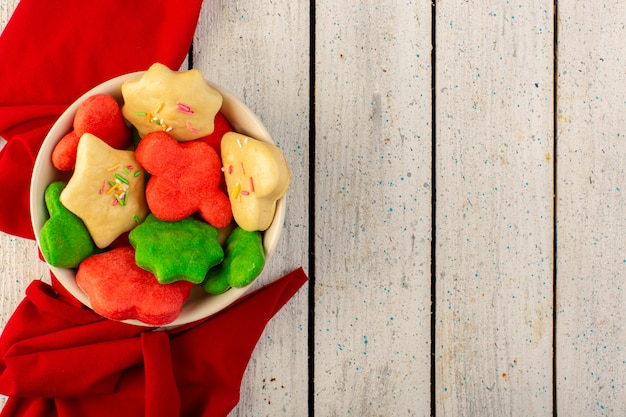 Vista superior de cookies deliciosos coloridos diferentes formados dentro da placa redonda na superfície cinza