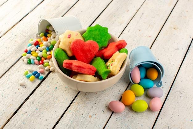 Vista superior de cookies deliciosos coloridos diferentes formados multicoloridos dentro da placa com doces na mesa cinza