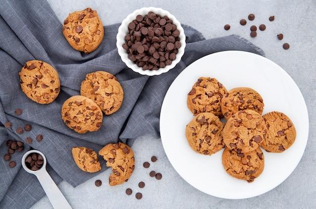 Vista superior de cookies e gotas de chocolate em um pano