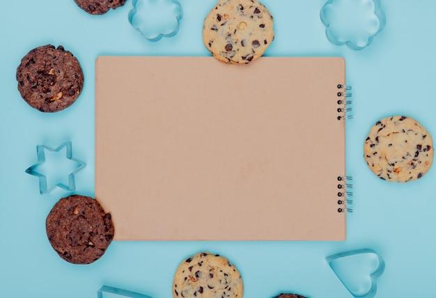 Vista superior de cookies em torno do bloco de notas sobre fundo azul, com espaço de cópia