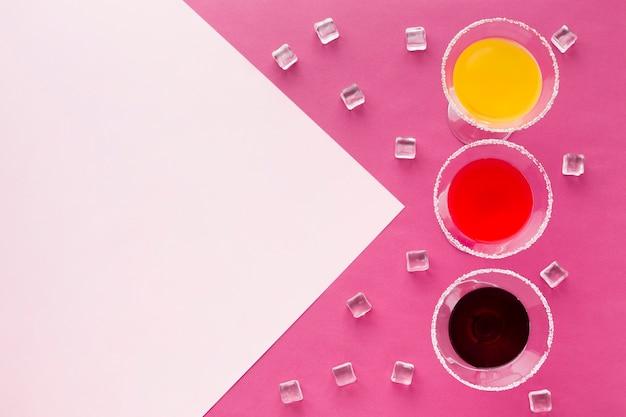 Vista superior de copos de coquetel com espaço de cópia e cubos de gelo