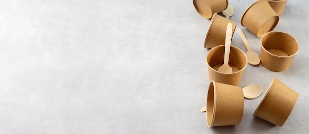Vista superior de copos de papel kraft eco e colheres de pau no fundo cinza