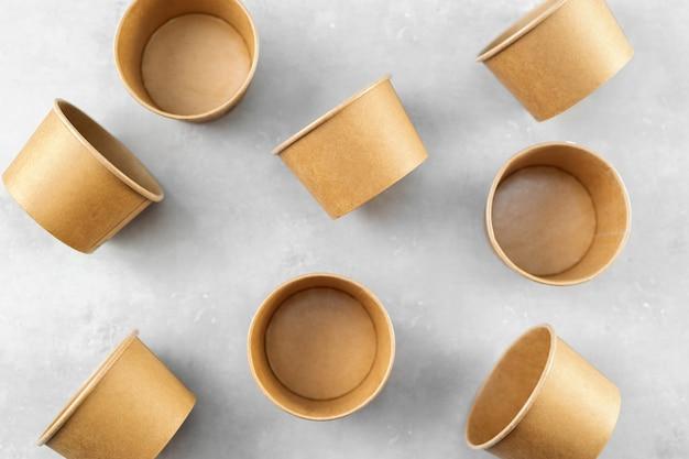Vista superior de copos de papel kraft eco em fundo cinza