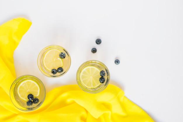 Vista superior de copos de suco de limão com tecido amarelo sobre fundo branco