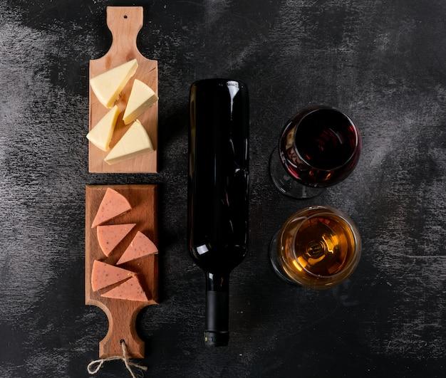 Vista superior de copos de vinho e queijo na tábua de madeira no escuro horizontal