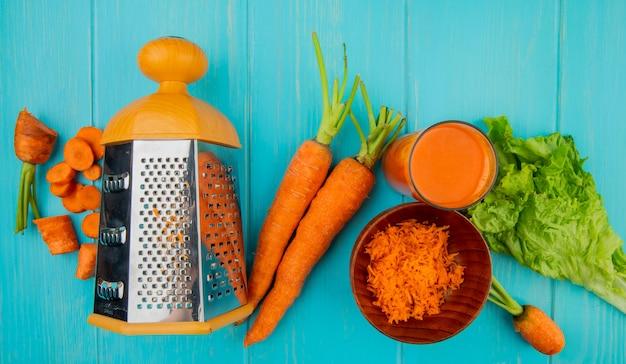 Vista superior de corte todo ralado cenouras fatiadas com ralador de metal alface e suco de cenoura na mesa azul