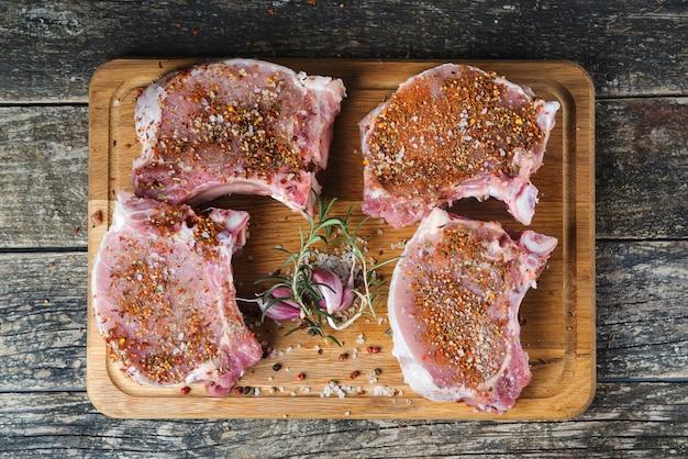 Vista superior de costela de porco fresca crua com especiarias. bife de carne fresca crua e cutelo de carne em fundo escuro.