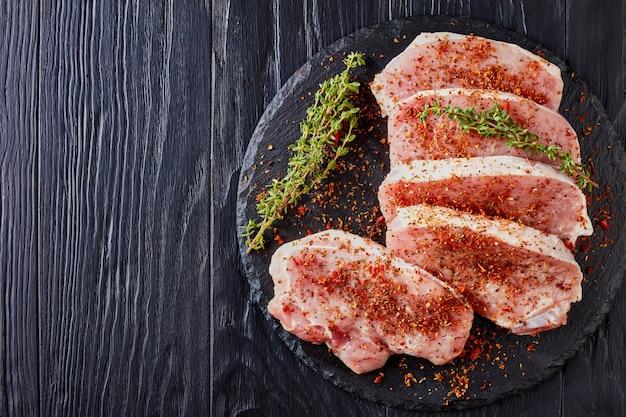 Vista superior de costeletas cruas de filé de porco, temperado com especiarias vermelhas secas: tomates, páprica, decorada com tomilho fresco, em uma placa de pedra redonda preta