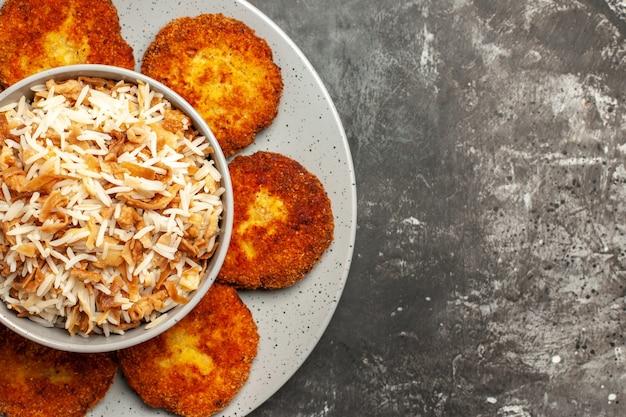 Vista superior de costeletas fritas com arroz cozido em rissole de carne para alimentos em superfície escura