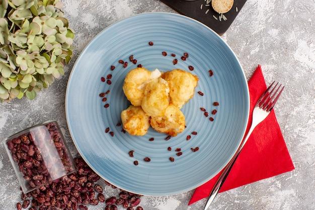 Vista superior de couve-flor cozida dentro de um prato azul com arroz e feijão em uma superfície clara
