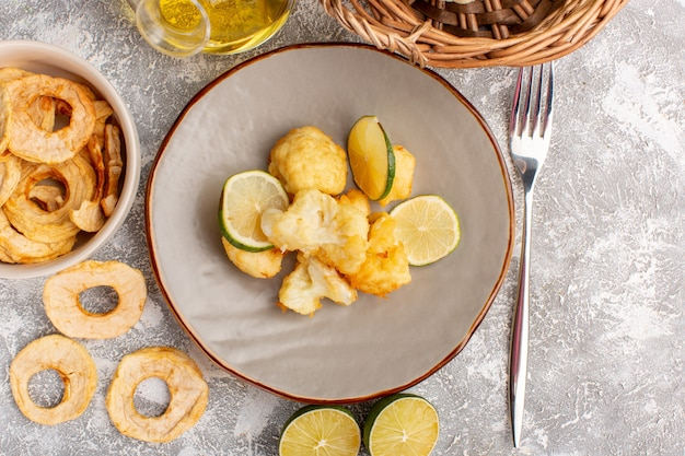 Vista superior de couve-flor fatiada cozida dentro do prato com limão e óleo na superfície branca clara